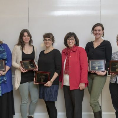 Image of six women, some holding plaques, listed left to right: Michelle Artibee, Tisha Bohr, Hale Tufan, Cornell President Martha E. Pollock, doctoral student Natalie Hofmeister, and Abby Cohn.
